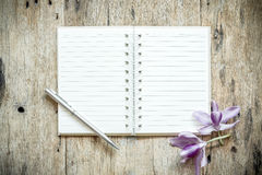 Blank notebook with orchids purple flowers on wooden table Royalty Free Stock Images