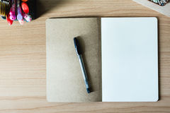 Blank notebook over wooden table. And a pen Stock Photo