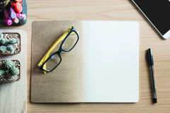 Blank notebook over wooden table. With a pen and smartphone Stock Photos