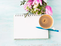 Blank notebook page with blue pen and cup coffee flowers. Blank empty notebook page with blue pen and cup of coffee. Spring summer flat lay with flowers royalty free stock images