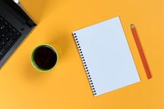 Blank notebook page, laptop, coffee cup and pencil. Blank writing pad for ideas and inspiration. On colored background stock image