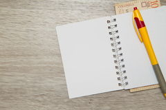 A blank notebook page and pen with Colombian pesos on wood office table. Top view with copy space Royalty Free Stock Image