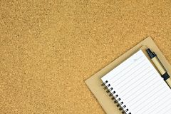 A blank notebook page and pen on cork board, Top view with copy space. Royalty Free Stock Photography