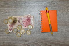 Blank notebook page and pen and Turkish Lira on wood office table. Top view with copy space. Stock Photo