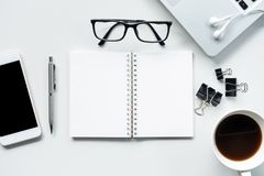 Blank notebook page is on top of white office desk table with supplies. Top view, flat lay.  royalty free stock photography