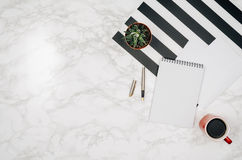Blank notebook page on white marble table background. Image taken from above, top view. Frame composition with copy space Stock Photo