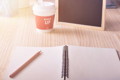 Blank notebook paper with pencil and hot coffee cup wake up message on office desk warm tone filter Stock Image
