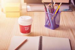 Blank notebook paper with pencil and hot coffee cup wake up message on office desk,warm tone filter Stock Photos