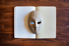 Blank notebook with papier-mâché mask stock photos