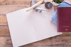Blank notebook,passport,compass,airplane and map on wooden table stock photography