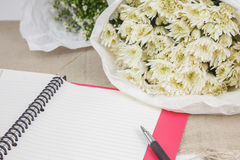 Blank notebook with pen and beautiful bouquet Royalty Free Stock Photography