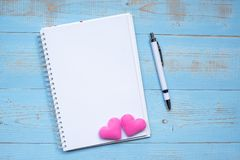 Blank notebook and pen with couple pink heart shape decoration on blue wooden table background. Wedding, Romantic and Happy royalty free stock photography
