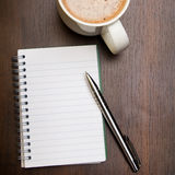 Blank notebook, pen and cup of coffee on wooden brown background Royalty Free Stock Photo
