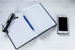 Blank notebook with pen. eyeglasses and mobile phone on wooden table Royalty Free Stock Image
