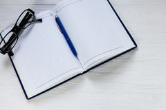 Blank notebook with pen and eyeglasses on wooden table Royalty Free Stock Photography