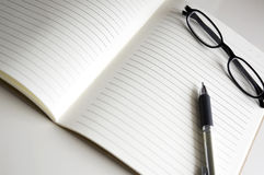 Blank notebook with pen and glasses Royalty Free Stock Images