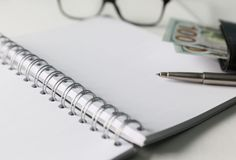 Blank notebook with pen and glasses. White blank notebook with silver pen and glasses. Some money and wallet are located close to it Stock Image