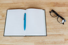 Blank notebook with pen and glasses on wood background Stock Image