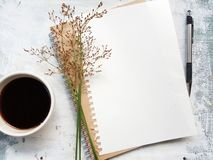 Blank notebook with pen next to a cup of coffee. stock photo
