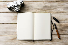Blank notebook, pen and old camera Stock Images