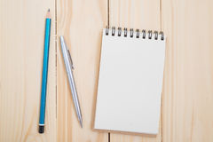 Blank notebook with pen and pencil on wooden table Stock Photography