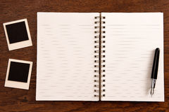 Blank notebook with pen and photo frames Royalty Free Stock Photography
