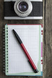 Blank notebook with  pen and retro camera on wooden table Stock Photography