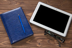 Blank notebook with pen and tablet computer on wooden brown table Royalty Free Stock Photography