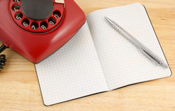 Blank notebook, pen and telephone on ta Stock Photos