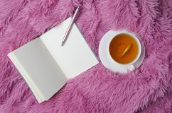 Blank notebook, pen, white cup with hop tea and lemon on fluffy plaid.Concept of girl`s planning royalty free stock photography