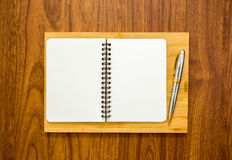 Blank notebook with a pen on wood background. Blank notebook with a pen on brown wood background Royalty Free Stock Photos