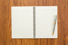 Blank notebook with a pen on wood background. Blank notebook with a pen on brown wood background Stock Photo