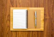 Blank notebook with a pen on wood background. Blank notebook with a pen on brown wood background Stock Images
