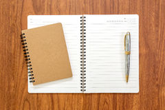 Blank notebook with a pen on wood background. Blank notebook with a pen on brown wood background Royalty Free Stock Photography