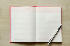 Blank notebook with pen on wood table Text input area royalty free stock images