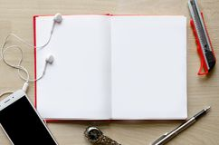 Blank notebook with pen on wood table And a wrist watch headset Modern phone Text input area stock photo