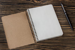 Blank notebook with pen on wooden table Royalty Free Stock Images