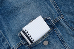 A blank notebook and pen in workmans jeans pocket. Stock Image