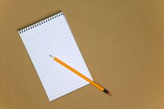 Blank notebook and pencil. Blank reporters notebook and pencil on a brown paper background Royalty Free Stock Photography