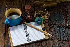 Blank notebook with pencil, coffee cup, hourglass and coffee beans on wooden table Royalty Free Stock Images
