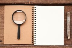 Blank notebook with pencil and magnifying glass. On wooden background Stock Image
