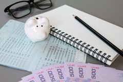 Blank notebook, pencil, savings account passbook, eye glasses, Thai money and piggy bank on gray background Stock Photography