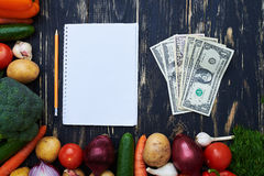 Blank notebook with pencil, some of money enclosed with a set of. Top view of blank notebook with pencil, some of money enclosed with a set of vegetables over Royalty Free Stock Photo