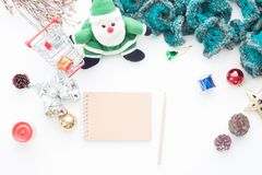 Blank notebook and pencil on white table with Christmas decorations and shopping cart Royalty Free Stock Photography