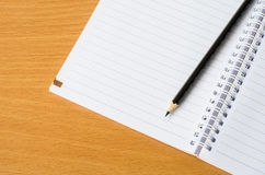 Blank notebook with pencil on wooden table Royalty Free Stock Images
