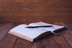 Blank notebook with pencil on wooden table. Selective focus stock image