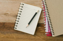 Blank notebook with pencil on wooden table - still lifeใ Royalty Free Stock Images