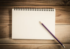 Blank notebook with pencil on wooden table - still life. Royalty Free Stock Photo