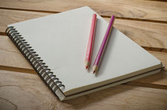 Blank notebook with pencil on wooden table - still life Stock Photo