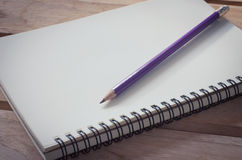 Blank notebook with pencil on wooden table - still life. Royalty Free Stock Images